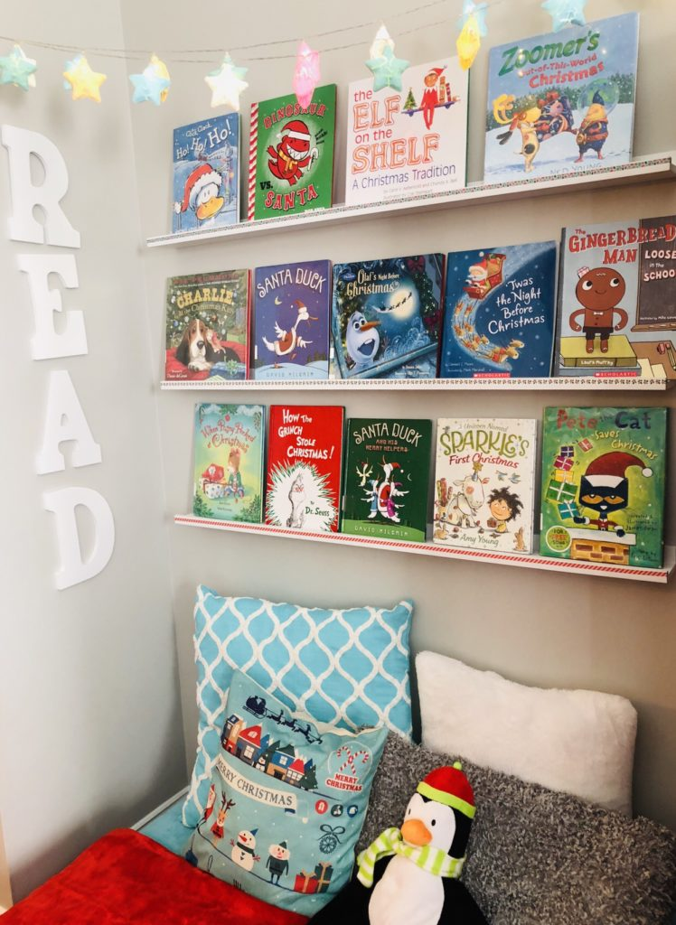 Create a Cozy Holiday Reading Nook with fun Christmas Themed books, pillows, and twinkle lights.