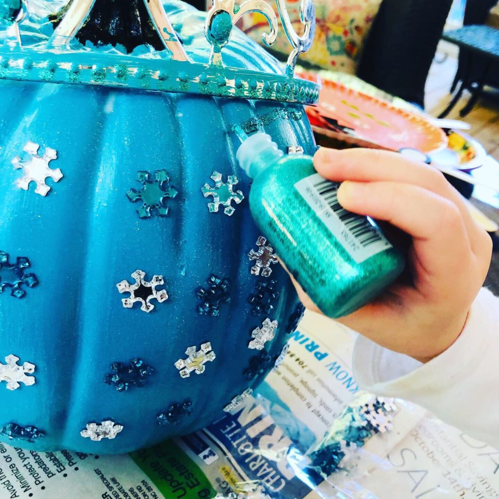 Adding a touch of glitter glue to the pumpkin