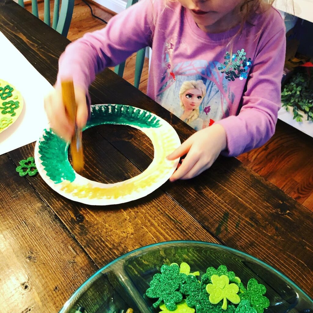 Creating a paper plate shamrock wreath for St. Patrick's Day